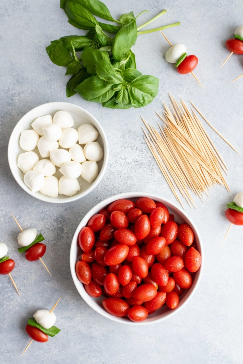 Overhead shot of Caprese Sticks ingredients - cherry tomatoes, mozzarella balls, basil, and toothpicks