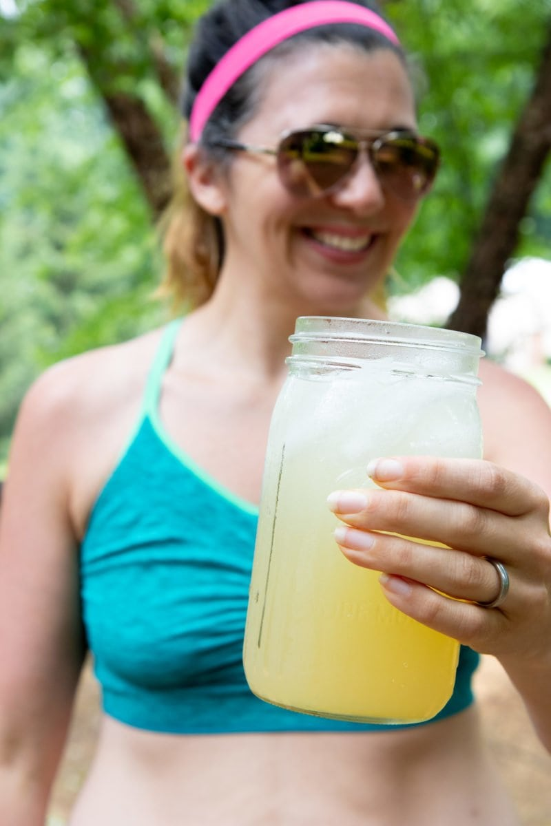 Woman in a turquoise sports bra smiling and holding a glass jar of Homemade All-Natural Electrolyte Drink
