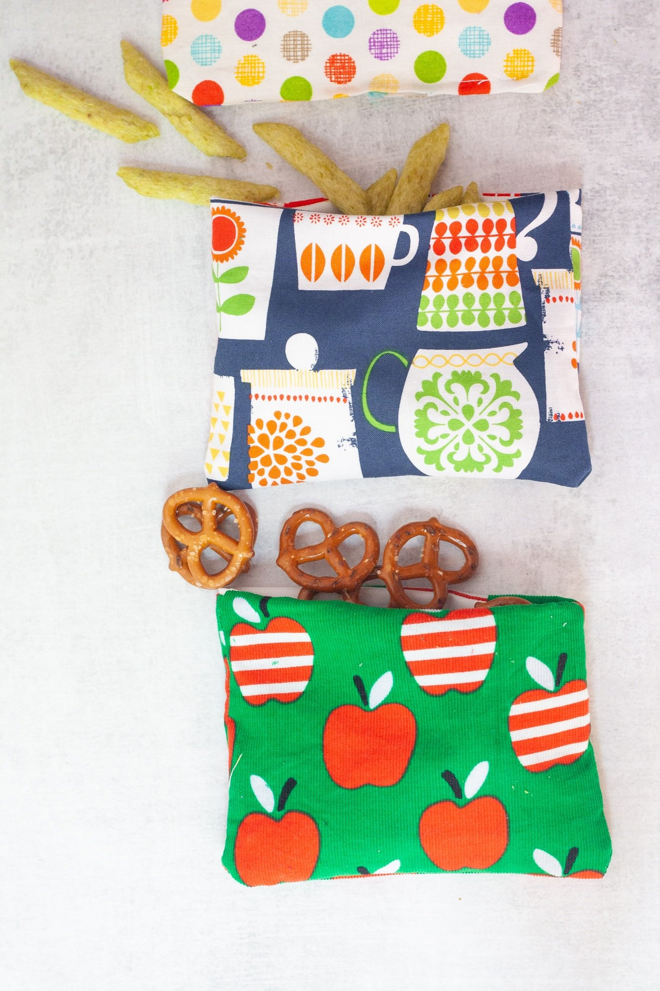 Reusable snack bags, each spilling out a different snack - pretzels and crispy snap peas