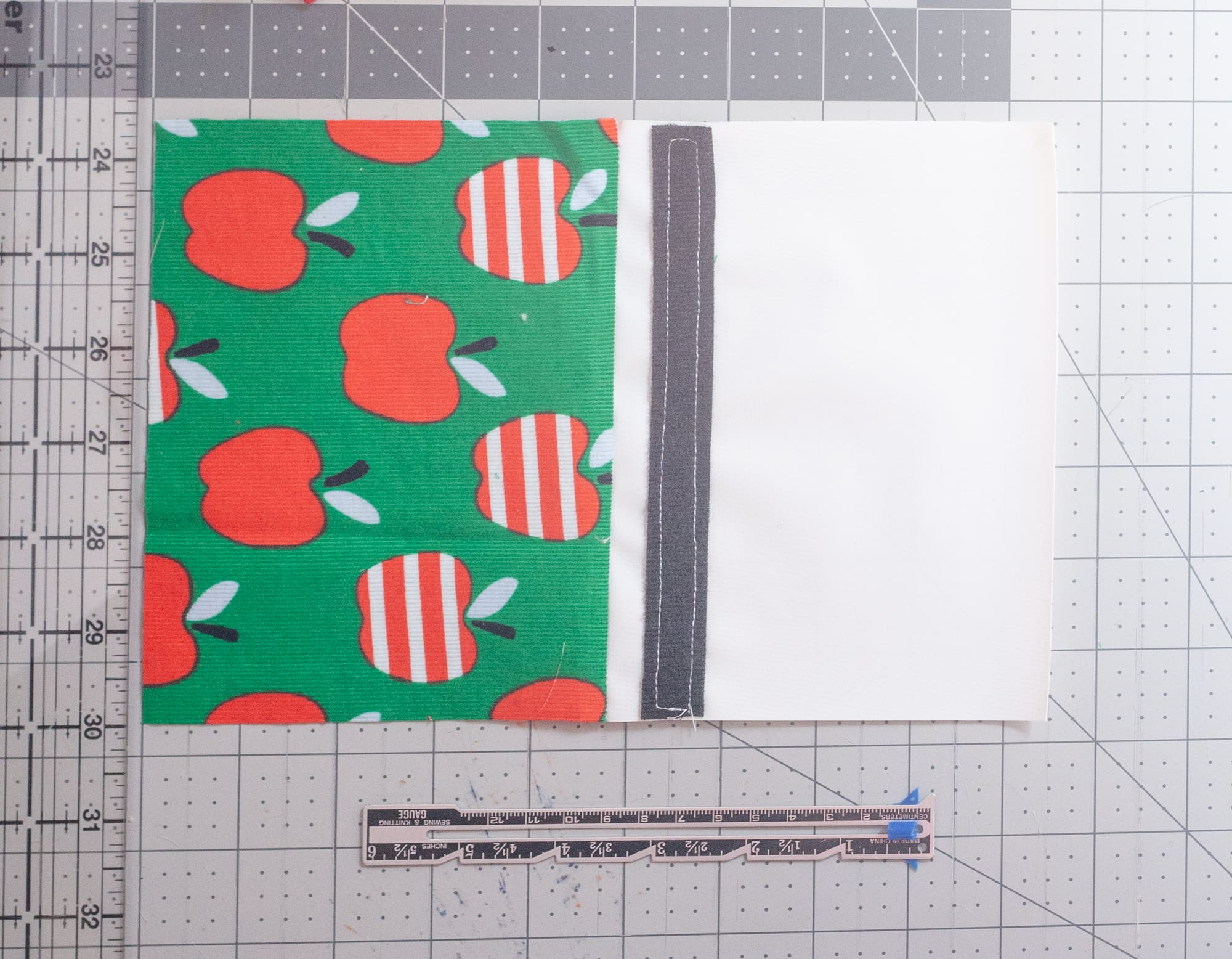 White fabric with a strip of Velcro sewn on to it, attached to a piece of apple-printed fabric