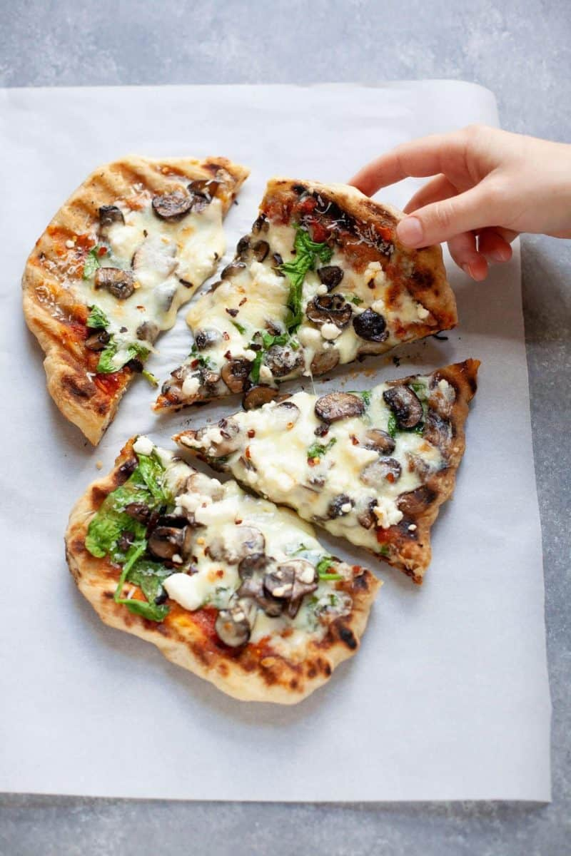 Overhead shot of a hand grabbing a slice of Grilled Flatbread Pizza with marinara, mushrooms, spinach, and goat cheese
