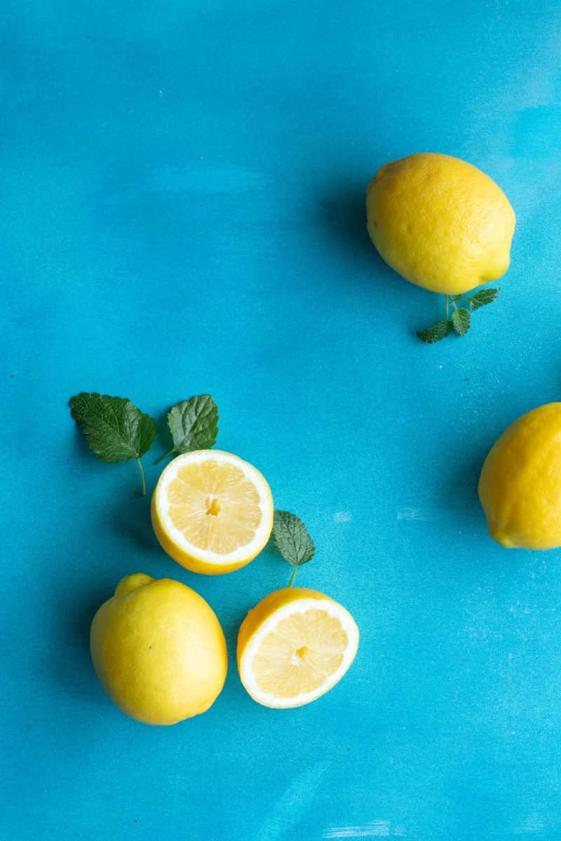 Overhead shot of whole and halved lemons on a blue background