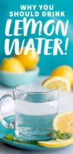 Side angle shot of a clear glass of lemon water on a blue plate, with more lemons and water in the background, with a text overlay