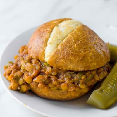 A finished lentil sloppy joe sits on a plate.