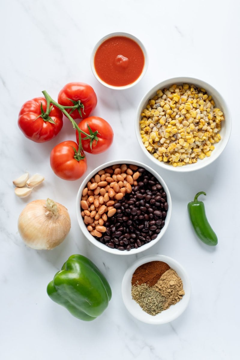Overhead shot of ingredients for Slow Cooker Summer Chicken Chili - tomatoes, beans, rice, onions, peppers