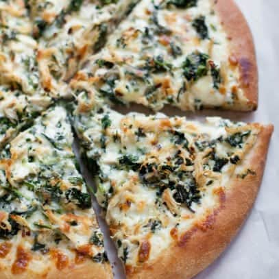Overhead shot of Chicken Spinach Alfredo Pizza, cut into slices