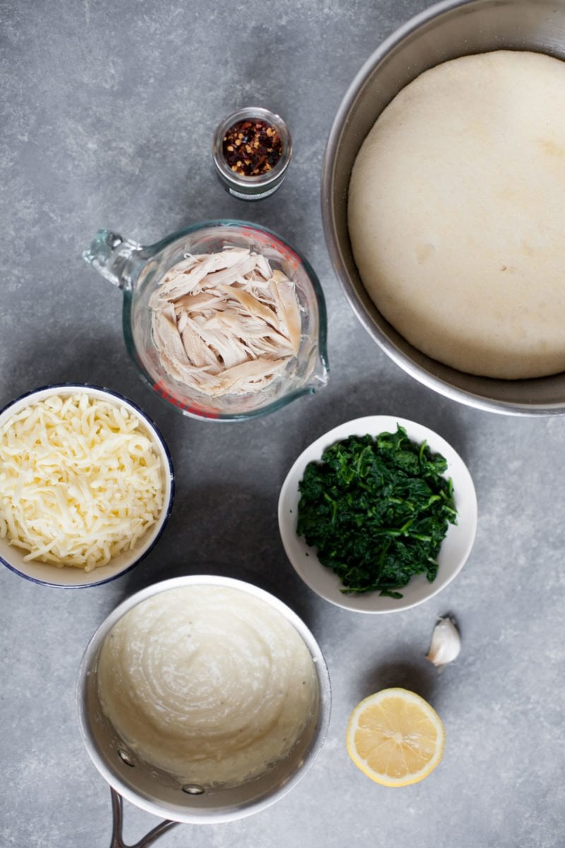 Overhead shot of pizza ingredients - chicken, spinach, alfredo sauce, cheese, pizza dough