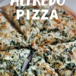 """Homemade pizza cut into slices. A text overlay reads """"Chicken Spinach Alfredo Pizza."""""""