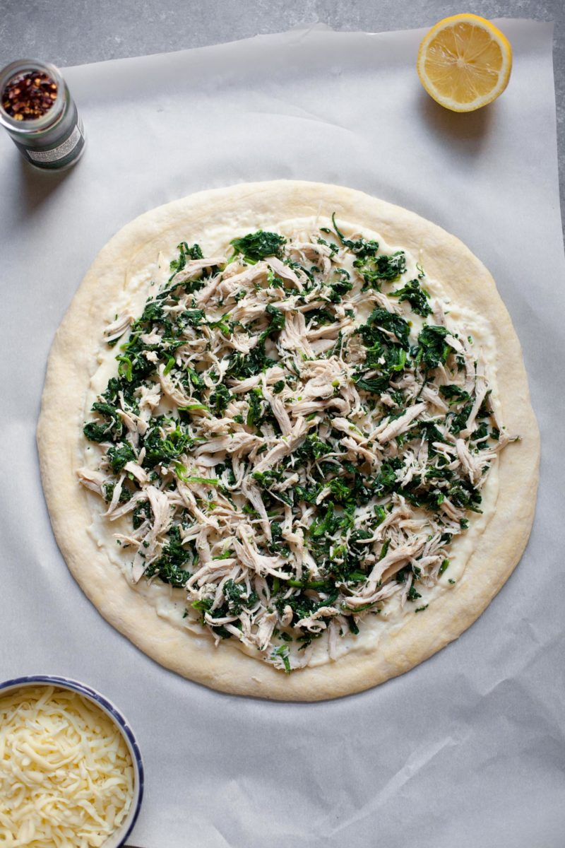 Overhead shot of uncooked Chicken Spinach Alfredo Pizza
