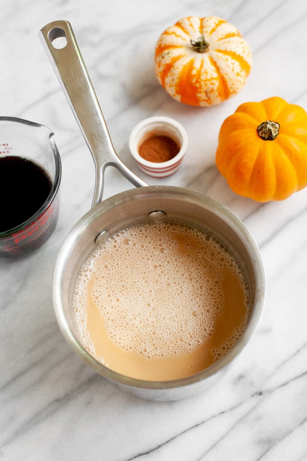 Vegan Pumpkin Spice Latte in a stainless steel saucepan, with coffee and mini pumpkins nearby