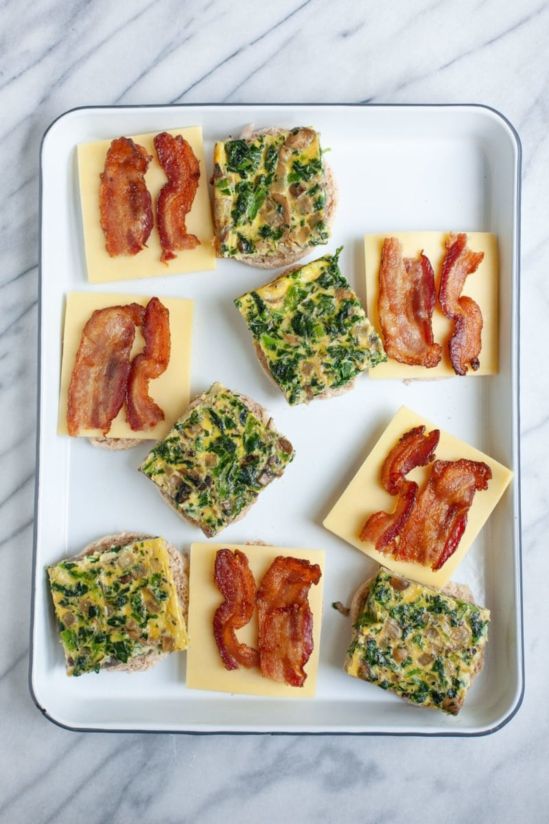 Overhead shot of open meal prep breakfast sandwiches with egg patties, cheese, and bacon on English muffins