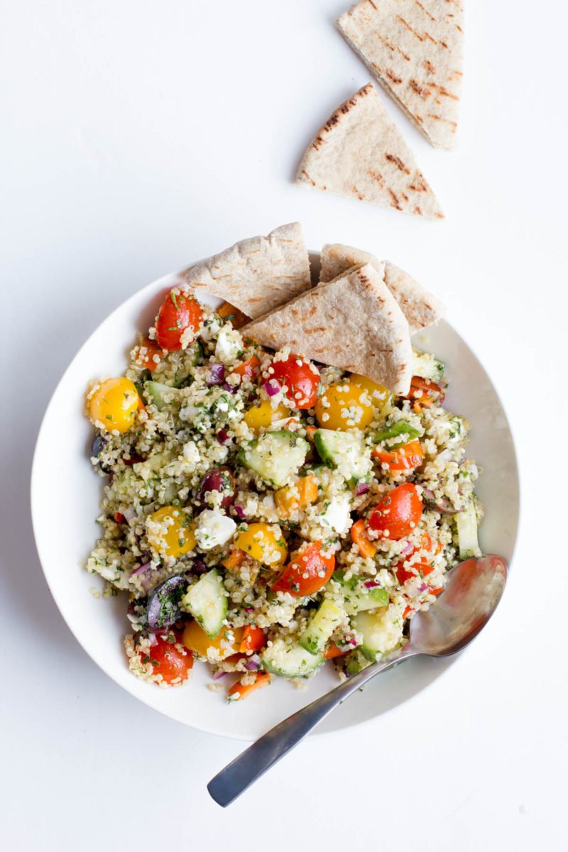 Overhead shot of Greek Quinoa Salad in a white bowl, with pita bread off to the side