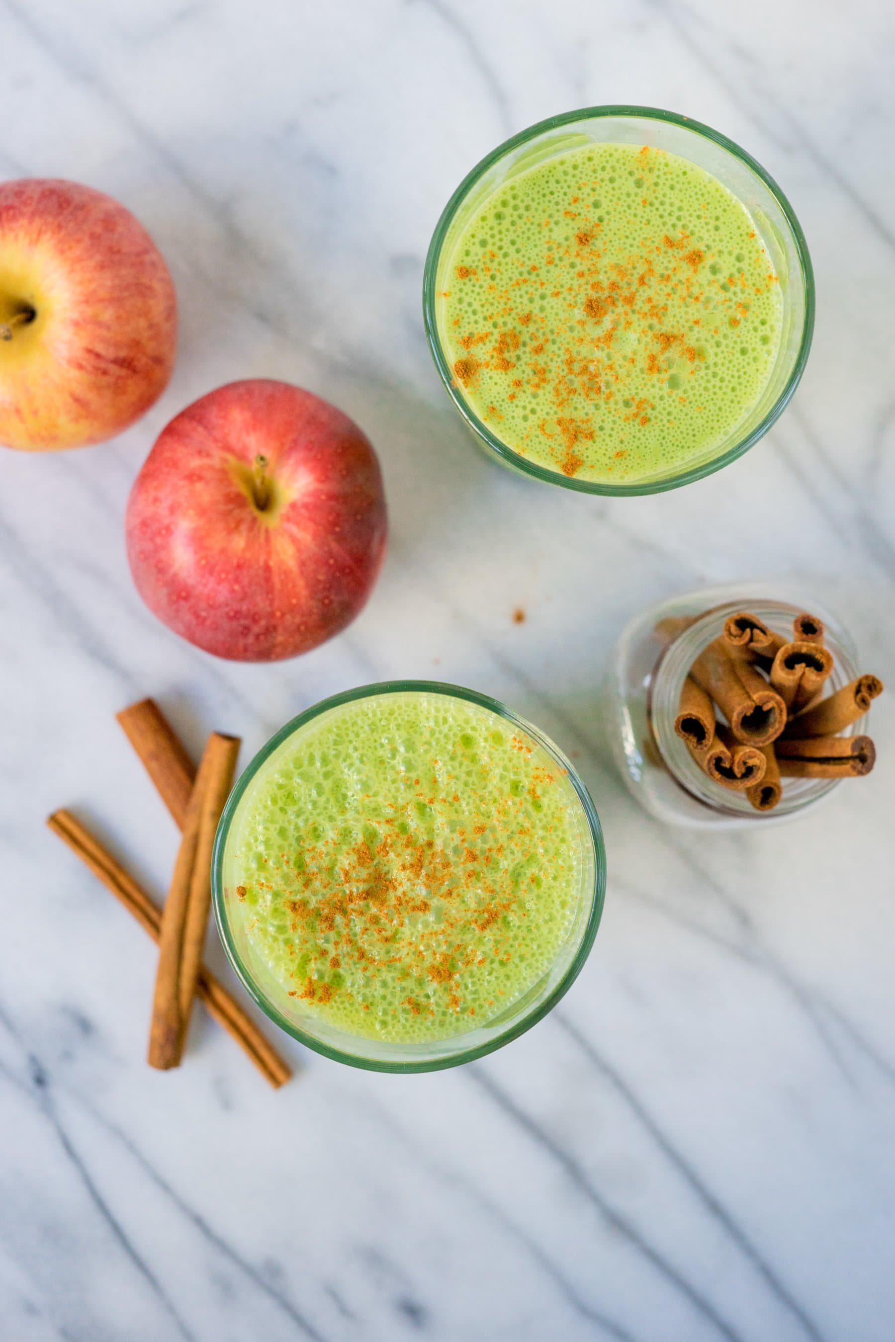 Overhead view of two glasses of green smoothie with apples and cinnamon sticks surrounding them