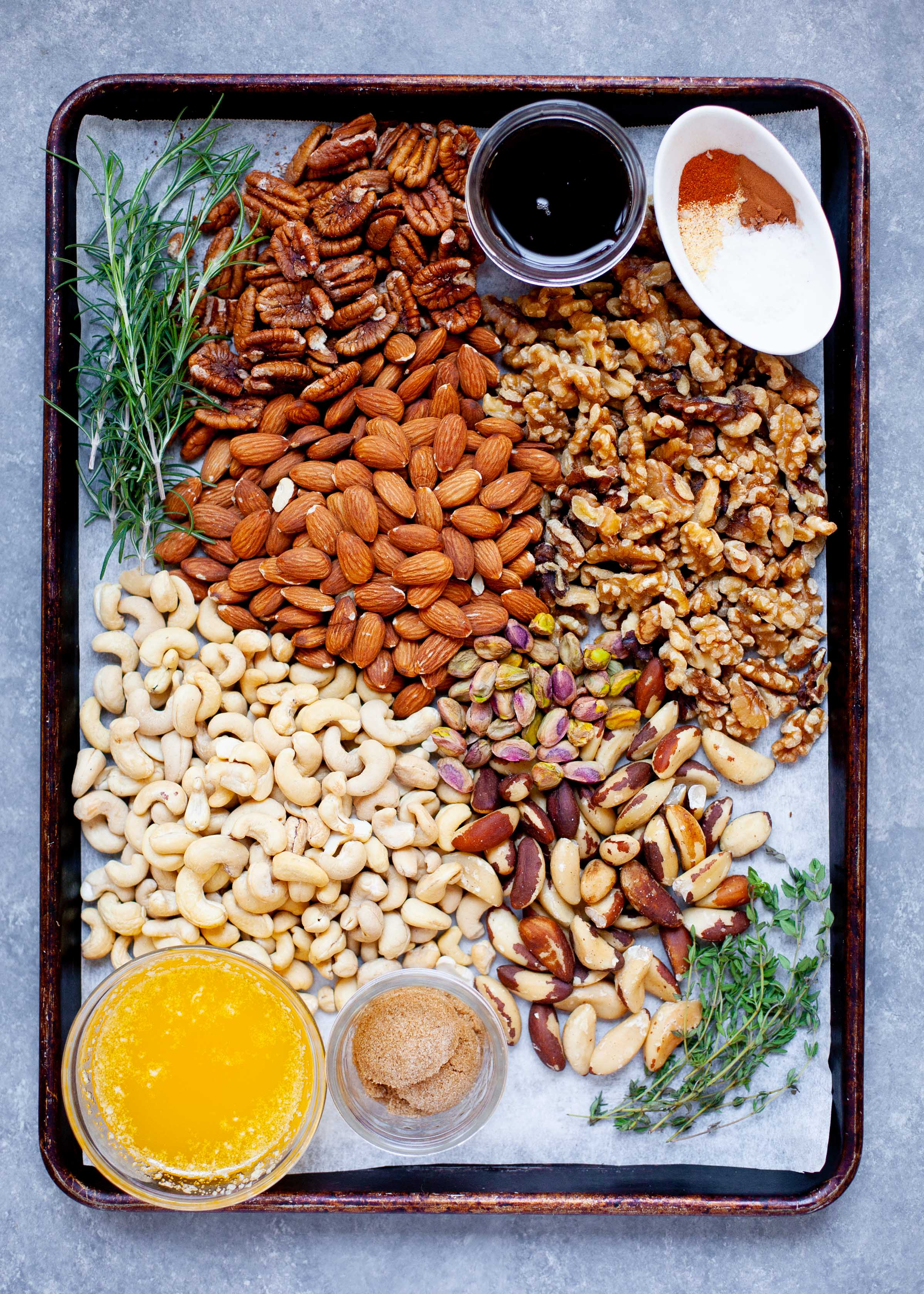 Ingredients for Maple Rosemary Bar Nuts on a white background - various nuts, rosemary, melted butter, brown sugar, rosemary, and spices