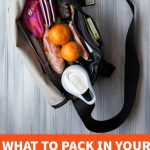 """Overhead shot of a black bag filled with a water bottle, clementines, and travel items. A text overlay reads """"What to Pack In Your Carry On"""""""
