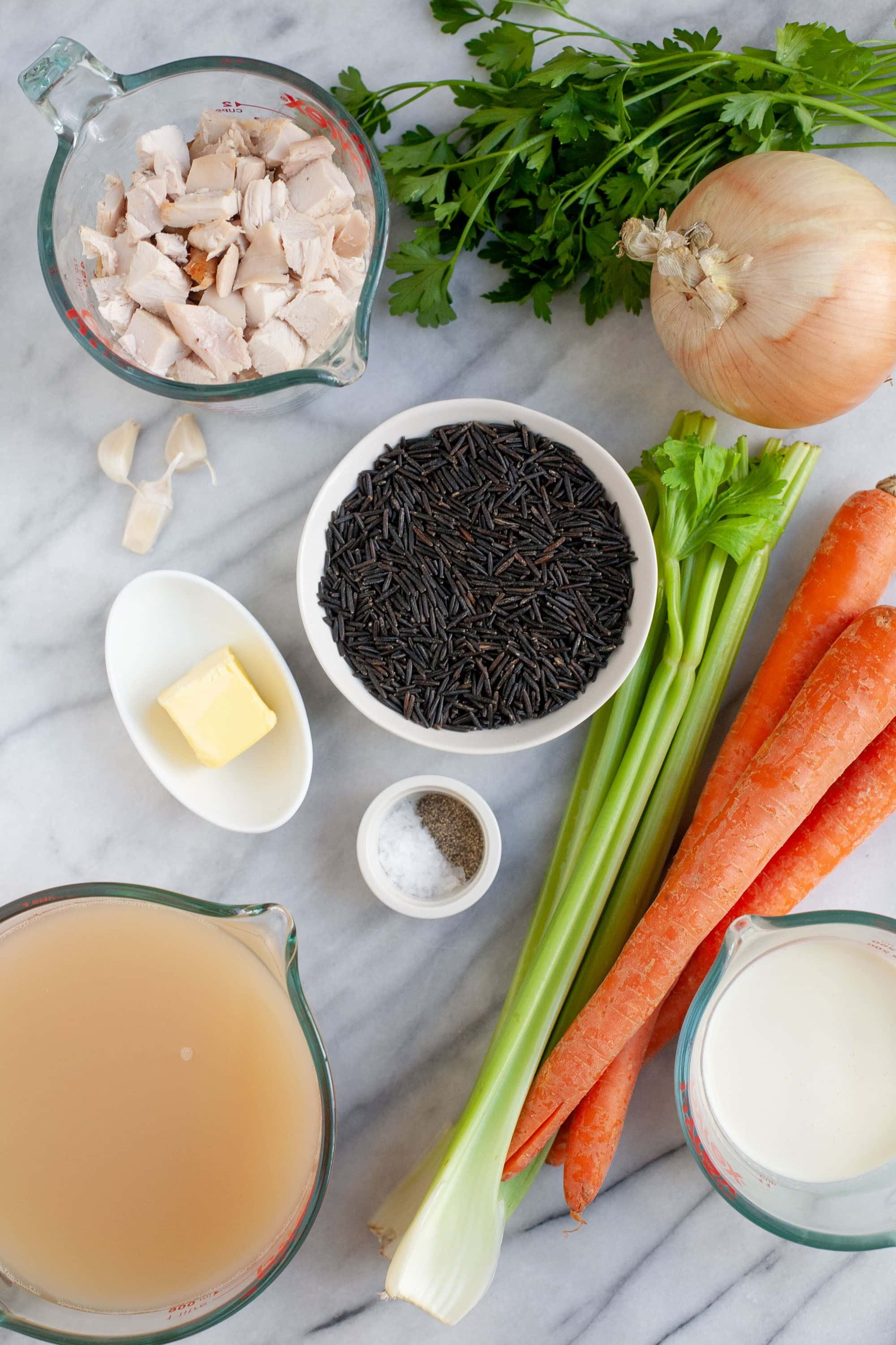 Ingredients for Cream of Turkey and Wild Rice Soup on a marble background - turkey stock, wild rice, vegetables, butter, turkey, spices