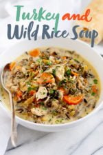 """Cream of Turkey and Wild Rice Soup in a white bowl with a spoon. Text overlay reads """"Turkey and Wild Rice Soup"""""""