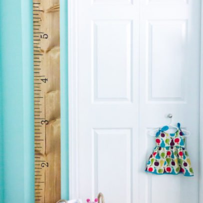 DIY Growth Chart Ruler hanging on a turquoise wall next to a white door.