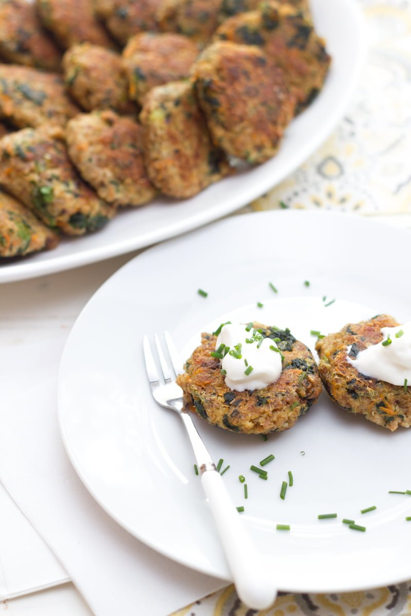 Spinach and Quinoa Patties on a white plate, topped with sour cream and chives