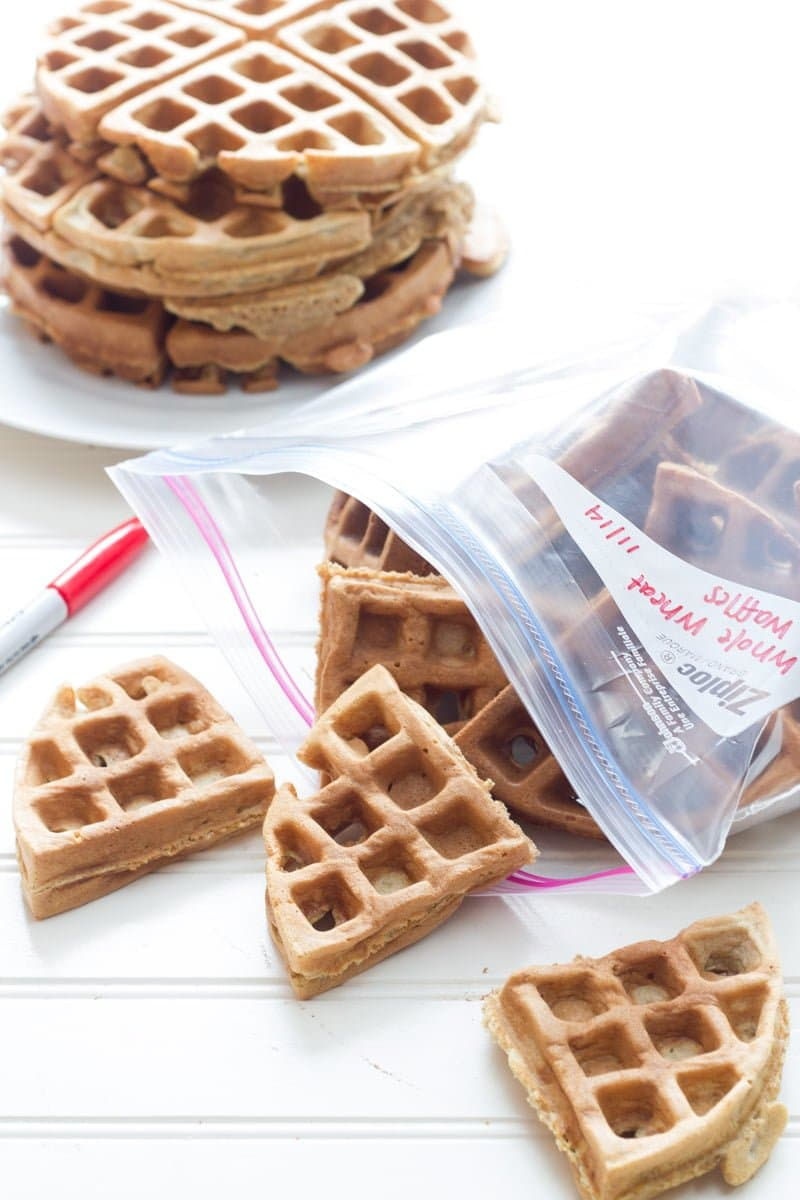 Whole Wheat Frozen Waffles sit cut into triangles in a ziplock bag. A stack of waffles sits in the distance.