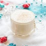 Glass of Coconut Milk Eggnog surrounded by blue and red holiday decorations.