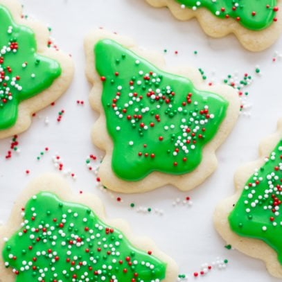 Decorated Christmas tree sugar cookies with green frosting and sprinkles rest on a white background.