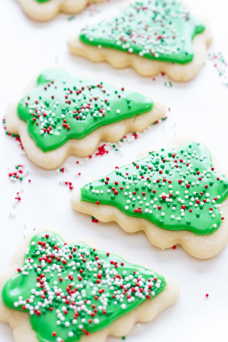 Decorated Christmas tree sugar cookies with green frosting rest on a white background.