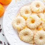 Clementine and Clove Spritz Cookies on a white plate with clementines and cloves nearby