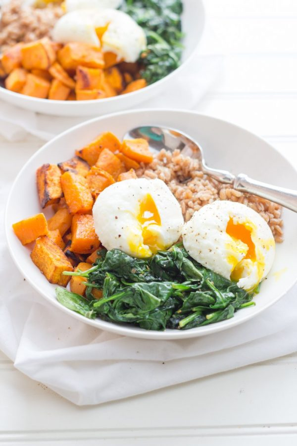 Curried Sweet Potato Breakfast Bowls in white bowls - cooked farro, roasted sweet potatoes, sauteed greens, and poached eggs