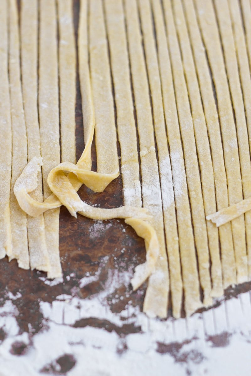 Uncooked homemade noodles sliced into thin ribbons.