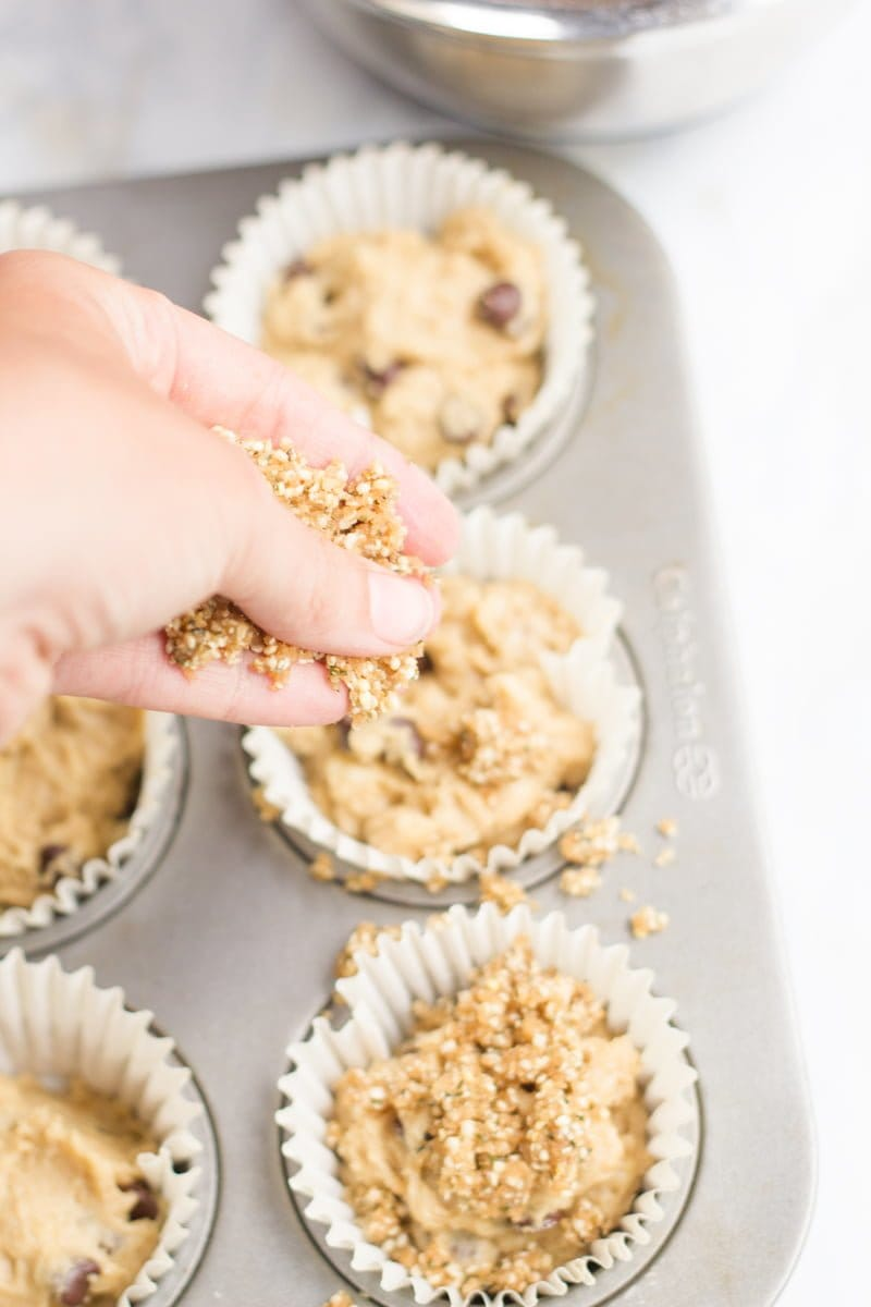 A hand pours hemp seed streusel on top of the Whole Wheat Banana Muffin dough