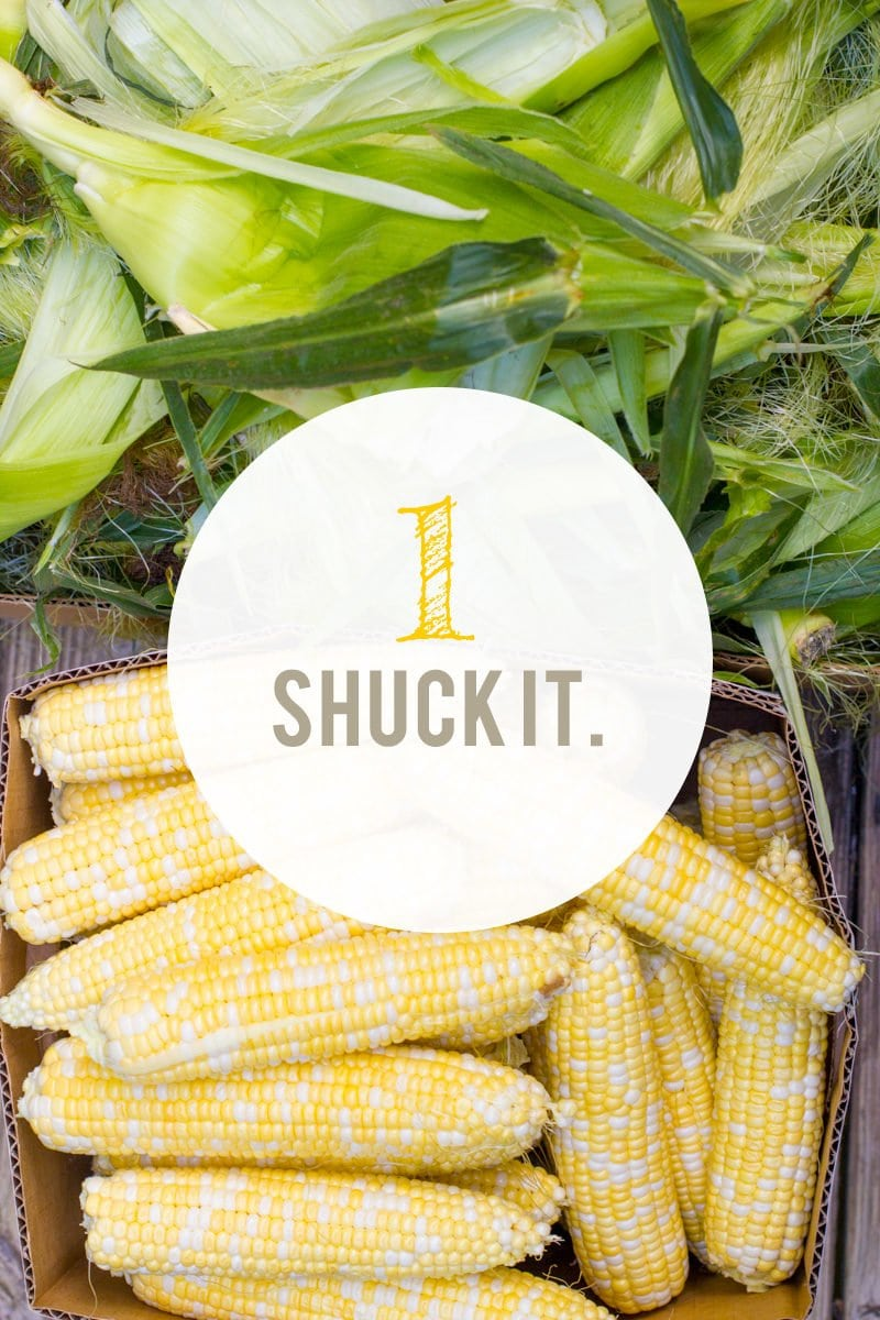 """Box full of corn, with the silks nearby. A text overlay reads """"1. Shuck It."""""""