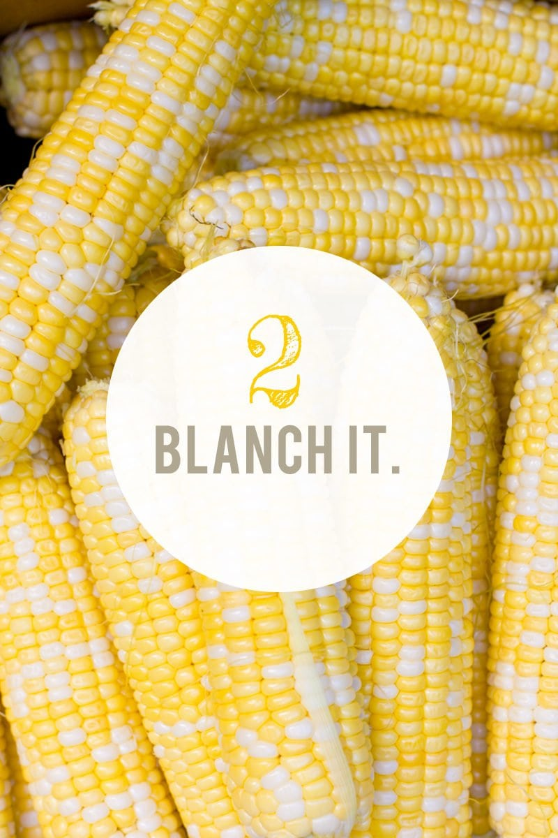 """Stack of shucked corn. A text overlay reads """"2. Blanch It."""""""