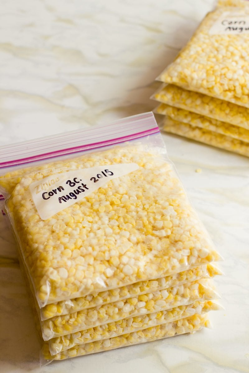 Stack of zip-top bags filled with corn kernels.