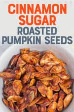 """White bowl filled with roasted pumpkin seeds. A text overlay reads """"Cinnamon Sugar Roasted Pumpkin Seeds."""""""