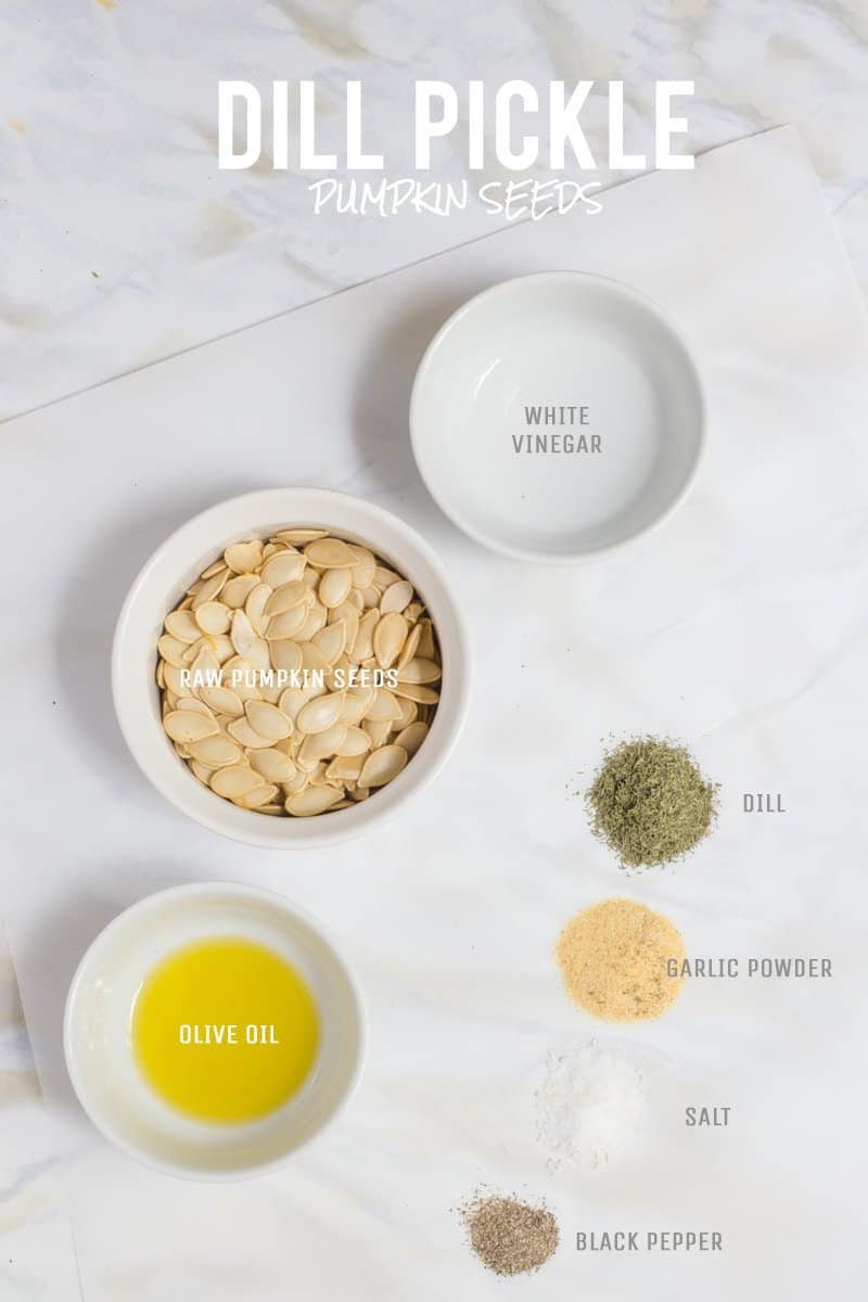 All ingredients for Dill Pickle flavored roasted pumpkin seeds are laid out on a white marble countertop.