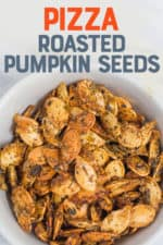 """White bowl filled with roasted pumpkin seeds. A text overlay reads """"Pizza Roasted Pumpkin Seeds."""""""