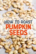 "Roasted seasoned pumpkin seeds on a parchment paper lined baking sheet. The pumpkin seeds are golden brown. A text overlay reads ""How to Roast Pumpkin Seeds."""