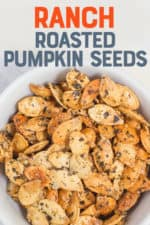 """White bowl filled with roasted pumpkin seeds. A text overlay reads """"Ranch Roasted Pumpkin Seeds."""""""