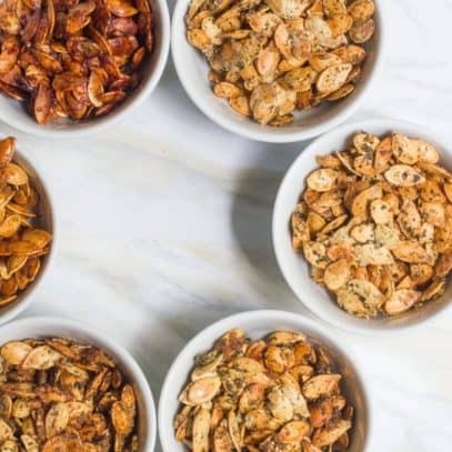 Six small white bowls filled with different flavors of roasted pumpkin seeds. Bowls are placed on a white marble countertop.