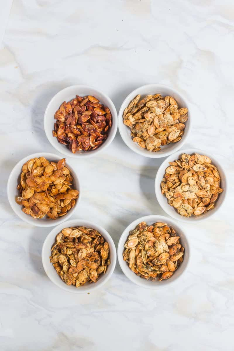 Six small white bowls form a circle on a white marble countertop. The bowls are filled with six different flavors of roasted pumpkin seeds.