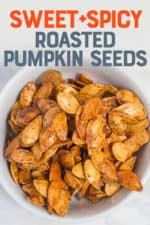 """White bowl filled with roasted pumpkin seeds. A text overlay reads """"Sweet + Spicy Roasted Pumpkin Seeds."""""""