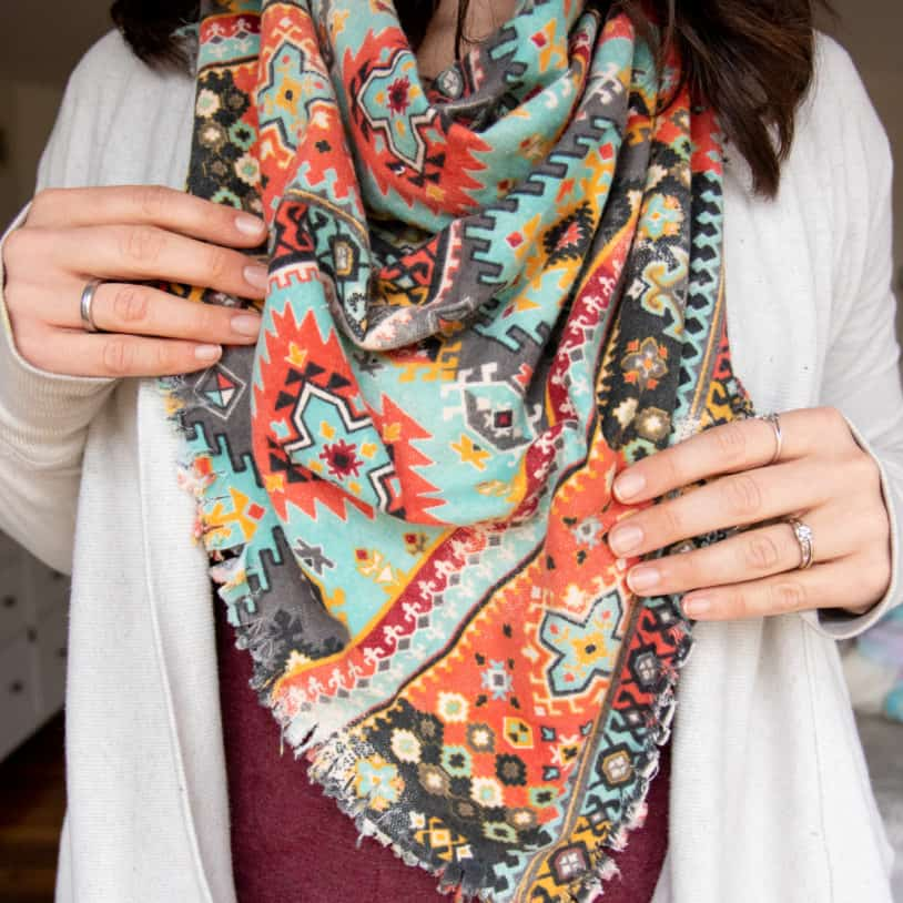 Woman with dark hair wearing a DIY flannel blanket scarf with an orange and teal Southwestern pattern over a burgundy shirt and ivory sweater.