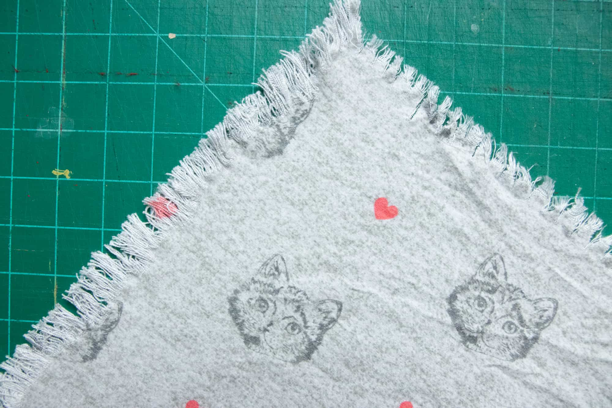 Tight view of the corner of a DIY blanket scarf after the edges have been frayed. The scarf is gray flannel with cats and hearts on it.