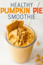 "Pumpkin smoothie in a clear glass with a straw on a white background. The smoothie is garnished with graham cracker pieces. A text overlay reads ""Healthy Pumpkin Pie Smoothie."""