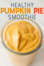 "Pumpkin smoothie in a clear glass on a white background. A text overlay reads ""Healthy Pumpkin Pie Smoothie."""