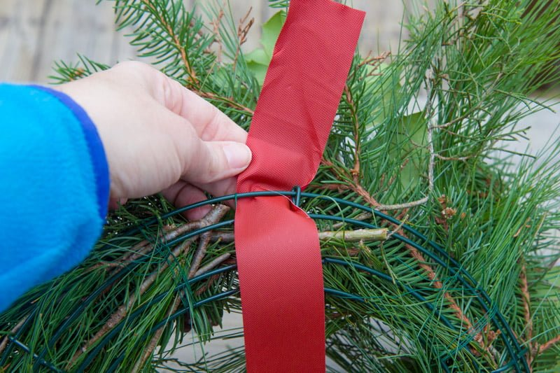 Hand tying a piece of ribbon to the back of a wreath form