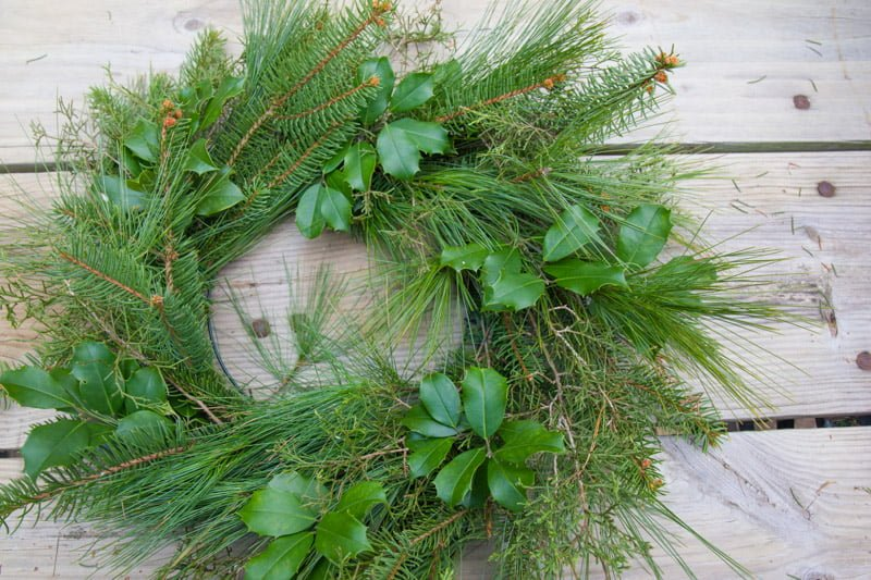 Wreath form completely covered in evergreens