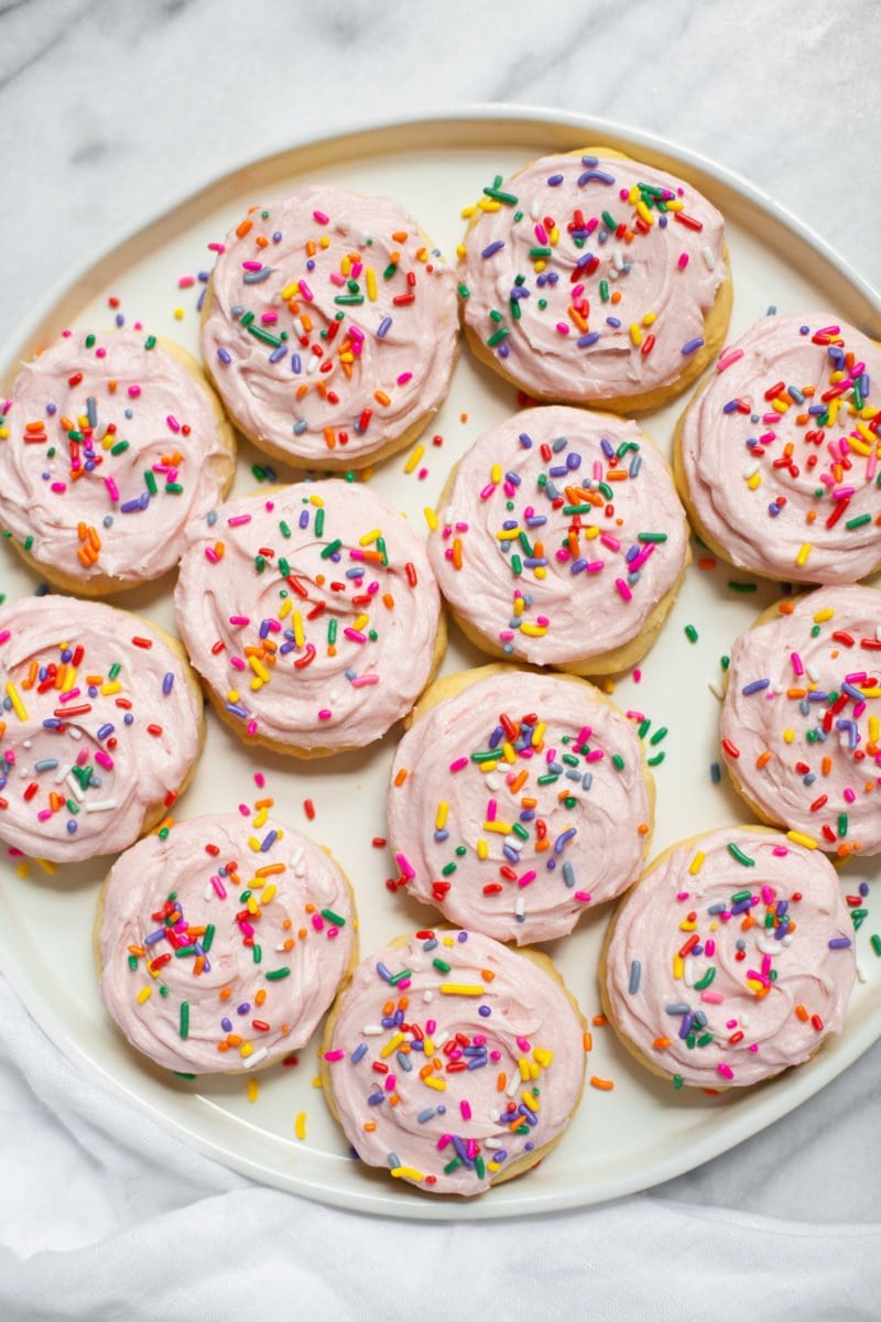 Lofthouse Sugar Cookies with pink frosting and rainbow sprinkles on a plate