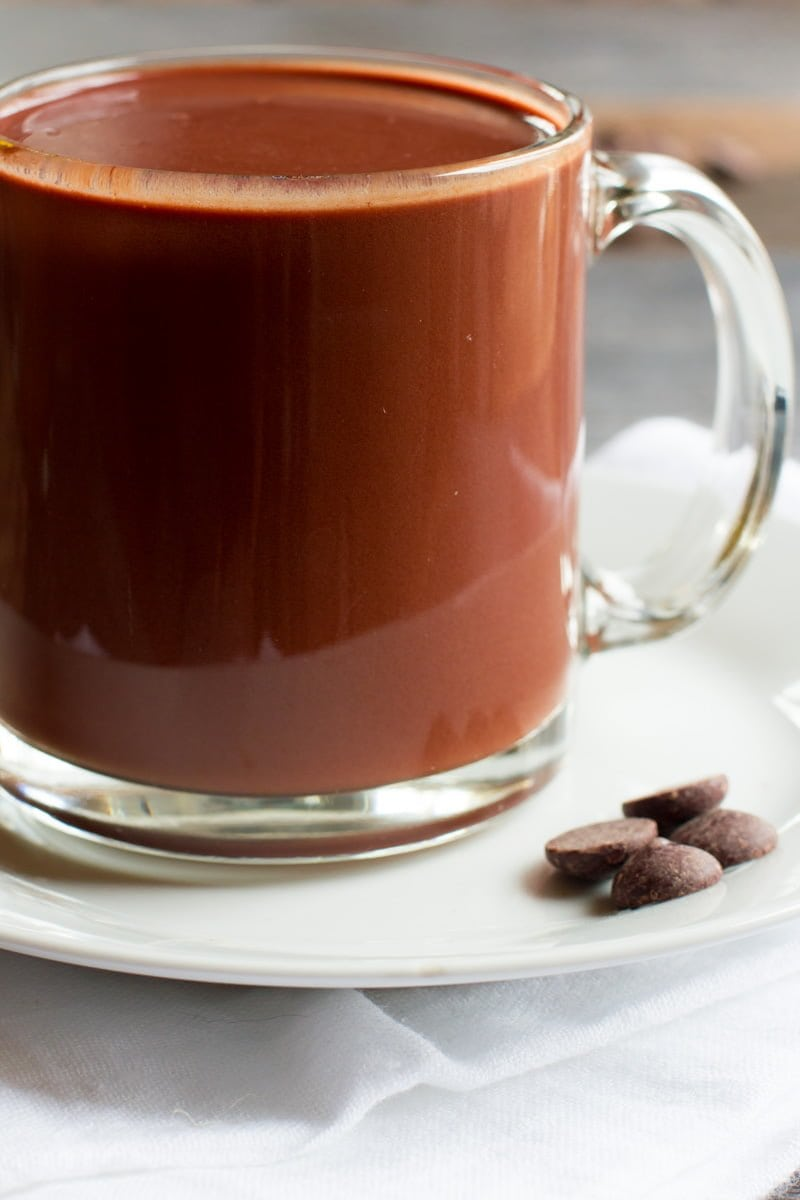 Clear glass mug of Red Wine Hot Chocolate next to chocolate chips